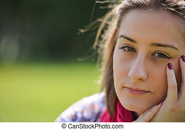 beautiful thoughtful young woman in the park on a warm summer day