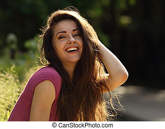 Beautiful toothy laughing enjoying young woman looking with long bright hair on nature bright sunny summer background. Closeup portrait