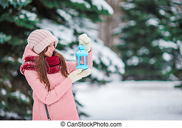 Beautiful woman holding Christmas candlelight outdoors on beautiful winter snow day