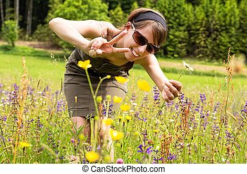 beautiful woman in a wildflower meadow shows victory symbol