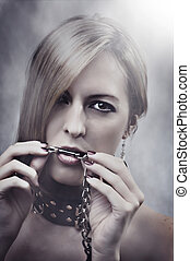 Beautiful Woman with chain in her mouth. Make up and manicure