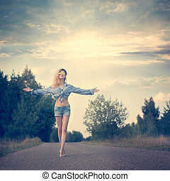 Beautiful Woman with Open Arms under the Sunrise