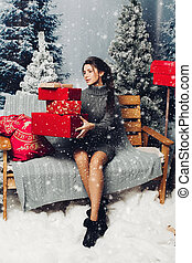 Beautiful woman with pile of Christmas presents.