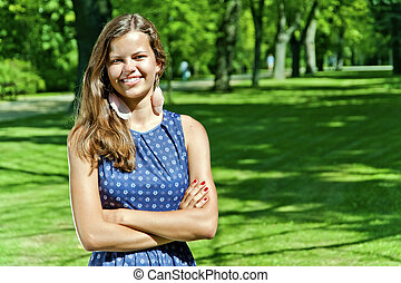 beautiful young brunette woman outdoor on the meadow on a summer day
