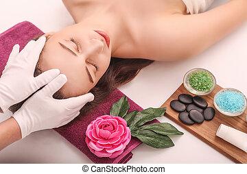 Beautiful young woman relaxing in the spa salon