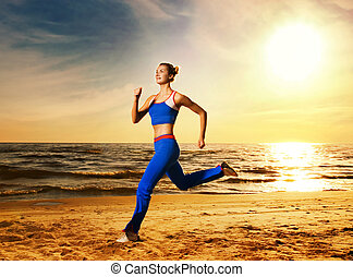 Beautiful young woman running on a beach at sunset