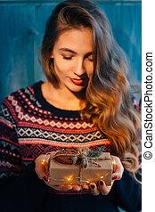 Beautifull girl holds a Christmas gift.