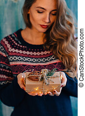 Beautifull woman holds a Christmas gift.