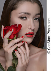 Beauty with rose. Portrait of beautiful women holding rose near her face while isolated on grey