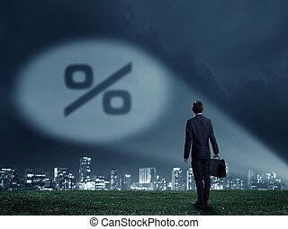 Businessman standing with back and percent sign in spotlight
