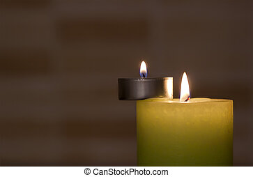 Big and little candles on dark background.
