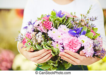 Florist holding big bouquet of fresh flowers