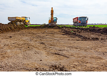 Big excavator is loading two trucks with ground on building site