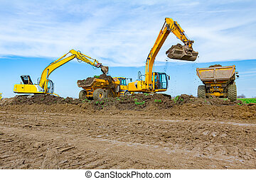 Big excavators are loading two trucks with ground on building site
