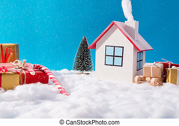 Big family celebrating christmas in little white house having smoke outdoors red brown gift box wooden sledges evergreen fir tree stand under blue sky background