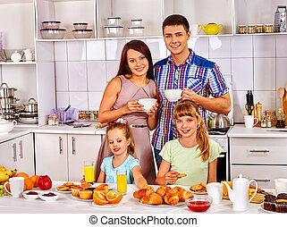 Big family with two kids having breakfast in the kitchen.
