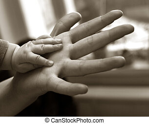 The image of hands of parents and the kid. b/w+sepia