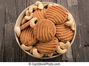 Biscuits and cashew in a bowl on a black wooden background