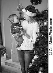 Black and white portrait of happy young mother in Santa hat and 10 months old baby son posing at Christmas tree in living room