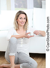 Blond woman sitting on the floor with coffee cup