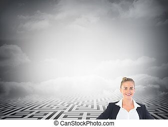 Composite image of blonde businesswoman standing with hands on hips in front of huge maze