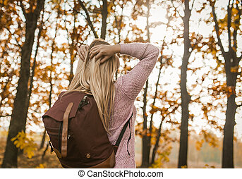 Young Woman With A Backpack Turned His Face To The Sun, Admires The Autumn Forest, Rear View Of Caucasian Blonde Putting Her Hands On Back Of Her Head While Relaxing On Autumn Trip
