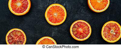 Blood Oranges. Halved blood oranges scattered on a black stone background. Banner
