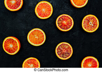 Blood Oranges. Halved blood oranges scattered on a black stone background. Top view, blank space.