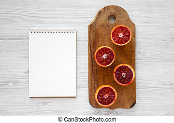Blood oranges halved on rustic wooden board, blank notepad over white wooden background, top view. Flat lay, overhead, from above.