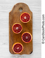 Blood oranges halved on rustic wooden board over white wooden background, top view. Flat lay, overhead, from above. Close-up.