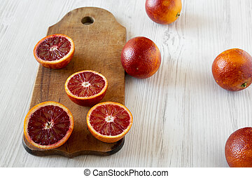 Blood oranges halved on rustic wooden board over white wooden surface, side view. Closeup.