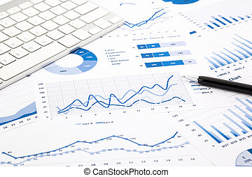 closeup blue graph and chart reports with white keyboard and pen on office table, financial and business concept