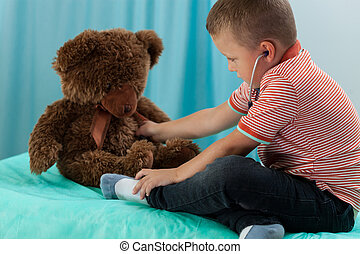 Boy examining teddy bear by stethoscope