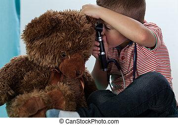 Boy examining teddy bear