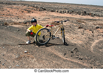 boy on a ride with its mountainbike along the coast side of lanzarote with helmet