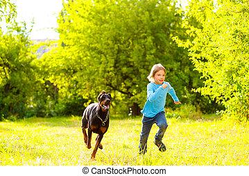 boy running away from dog or doberman in summer park