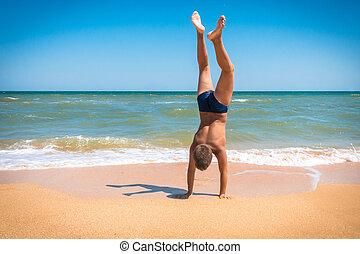 Boy standing upside down on the beach