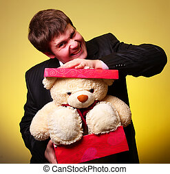 Boy with present box and teddy bear can't select a present in St. Valentine day