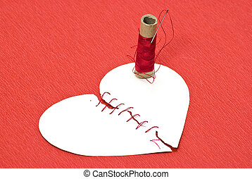 Broken heart and threads on red background