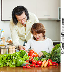 woman with handsome husband cooking with fresh vegetables