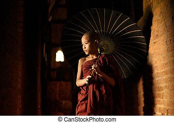 Buddhist novice walking with umbrella