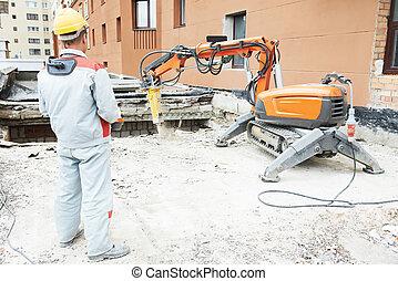 builder worker operating demolition machine