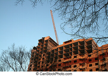 Building site and hoisting crane on background with blue sky and trees
