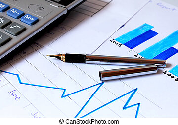 pen placed over financial statistics and charts