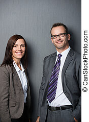 Business couple leaning against a wall