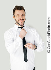 Business dressing up. Handsome young man in formalwear adjusting his necktie and looking at camera while standing against grey background