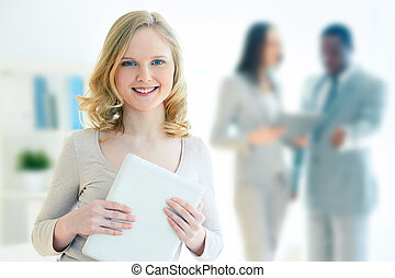 Portrait of a lovely business intern holding a touchpad