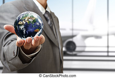 """business man holds globe in the airport""""Elements of this image furnished by NASA"""""""