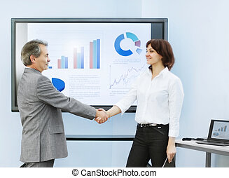 business partners shake hands after a successful presentation