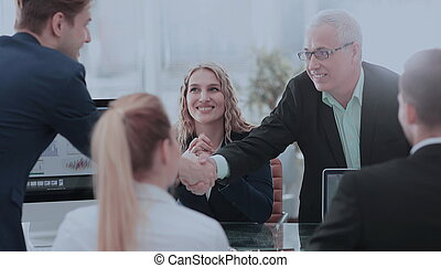 Business partners shaking hands after a successful transaction.